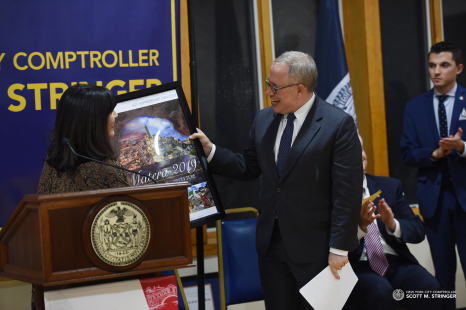 October 2019 - New York City Comptroller Scott Stringer proudly shows the annual theme poster at his Proclamation Ceremony as IHCC-NY, Inc. Board member Cav. Joan Marchi Migliori presents it.